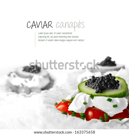 Freshly prepared black caviar and soft cheese canapes styled on scallop shell in snow. The perfect image for a restaurant menu cover or dinner invitation. Copy space.  - stock photo