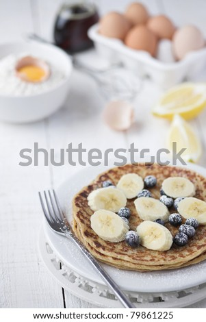 Freshly prepared crepes with banana & blueberries - shallow dof - stock photo
