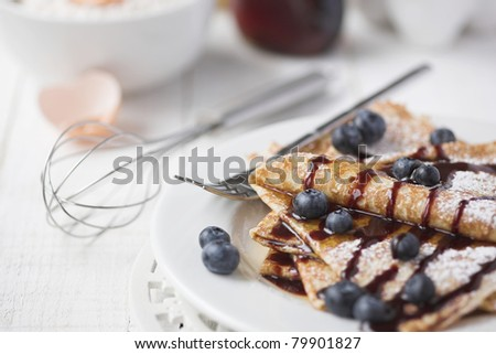 Freshly prepared crepes with blueberries & chocolate sauce - shallow dof - stock photo