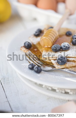 Freshly prepared crepes with blueberries - shallow dof - stock photo
