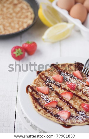 Freshly prepared crepes with strawberries - shallow dof - stock photo