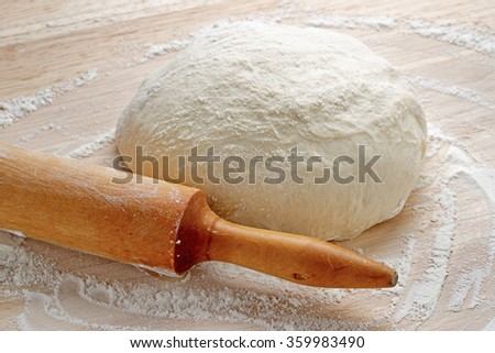 Freshly prepared dough on a wooden board. Rolling pin and flour on table.