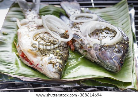Freshly prepared fish on barbecue with vegetables and lemon. The fish is on banana leaf - stock photo