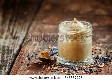 Freshly prepared mustard sauce in a small glass jar with a spoon and scattered the seeds of the black and yellow mustard on an old wooden table, selective focus - stock photo