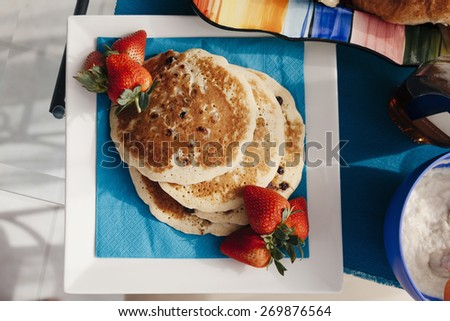 Freshly Prepared Pancakes With With Raisins And Strawberries Around - stock photo