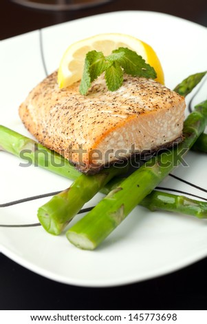Freshly prepared salmon dish on a bed of asparagus spears. - stock photo