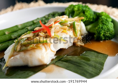 Freshly prepared Thai style sea bass fish dinner with asparagus and appetizer with a contemporary presentation. - stock photo