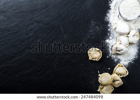 Freshly prepared Tortellini on a slate, with ingredients - stock photo