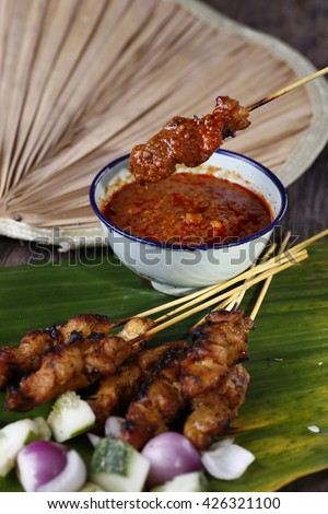 freshly roasted chicken satay served with chilli peanut gravy with onions and cucumber and ketupat sold at night market street food stalls in malaysia - stock photo