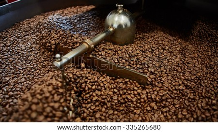 Freshly roasted coffee beans in a coffee roaster. Shallow dof - stock photo