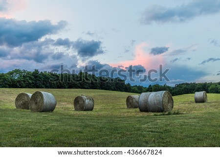 Freshly rolled bales of hay are seen on a rolling hill during a beautiful sunset - stock photo