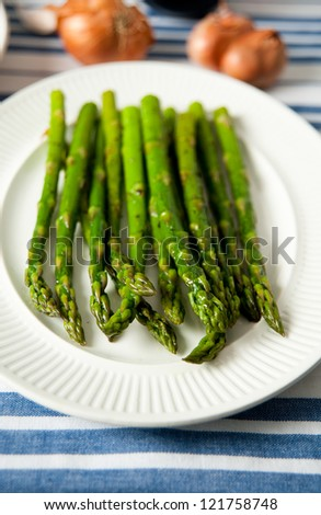 Freshly Sauteed Asparagus Served on White Plate - stock photo