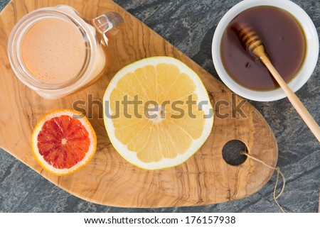 Freshly squeezed grapefruit juice served with a container of honey and two halved grapefruit on an old olive wood chopping board for a healthy breakfast, overhead view - stock photo