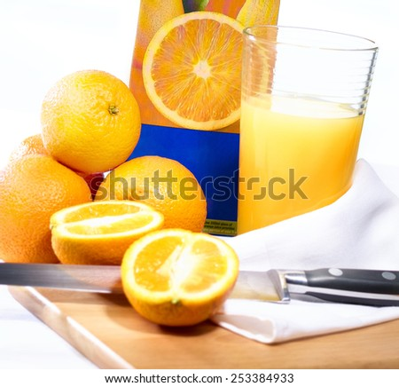 Freshly squeezed orange juice in highball tumbler glass on chopping block with whole and half sliced oranges, knife, carton and hand towel isolated
