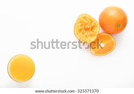 Freshly squeezed orange juice with cut oranges on white background - stock photo
