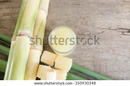 Freshly squeezed sugar cane juice in glass with cut pieces cane on a wooden table.