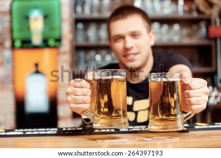Freshly tapped beer. Selective focus on close up of glasses with beer which cheerful young bartender stretches out and smiles