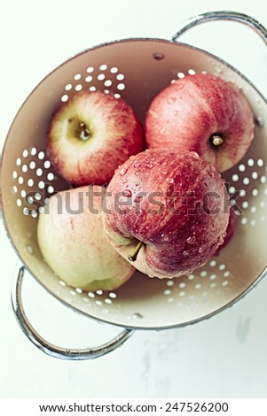 Freshly washed apples in a colander  - stock photo
