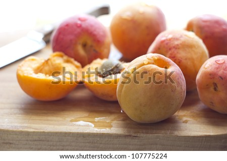 Freshly washed apricots on wooden cutting board with knife. Macro with shallow dof - stock photo