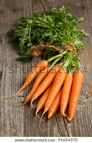 Freshly washed whole carrots on old wooden table - stock photo