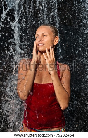 Freshness concept - Young and emotional girl in red tank-top enjoying jungle waterfall - stock photo