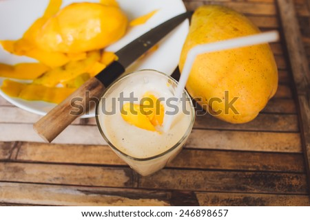 freshness fruit mango  lying on a white plate with knife. Fresh shake with shape heart love  mango slices milk and straw on brown board rustic