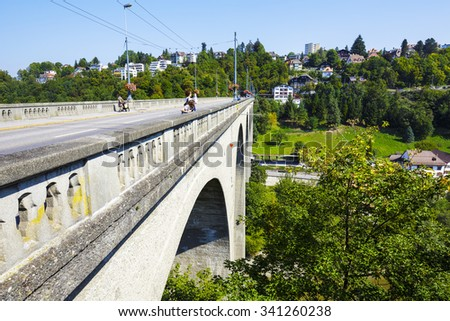 FRIBOURG, SWITZERLAND - SEPTEMBER 10, 2015: Zaehringen Bridge. The bridge is 165m long and spans both sides of the river Sarine which shares two linguistic regions between German and French cultures - stock photo