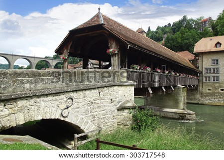 FRIBURG, SWITZERLAND - JUNE 16, 2015: Bern Bridge(Pont de Berne). The last covered wooden bridge in Fribourg dates back to 1653.One of the few remaining wooden bridges                                  - stock photo