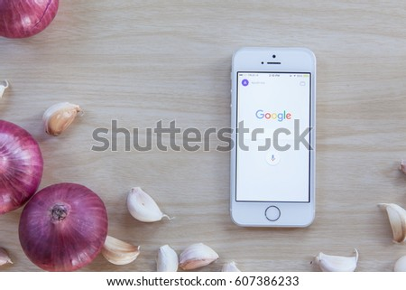 Friday, 24 March 2017: in Chiang Mai Thailand, Google application  is launching on Smartphone on wooden kitchen table.