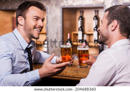 Friday night fun. Two cheerful young men in shirt and tie talking to each other and gesturing while drinking beer at the bar counter  - stock photo