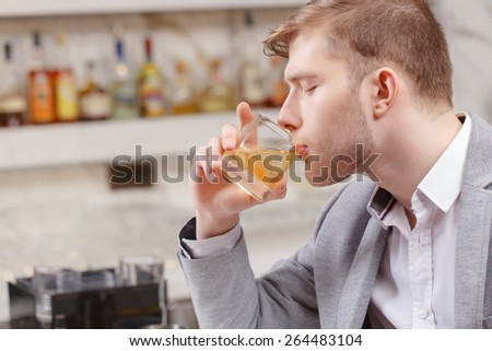 Friday night. Young man in shirt and jacket drinking whiskey with ice sitting at the bar counter - stock photo