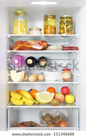 Fridge open full stocked  loaded up with food and fresh ingredients. - stock photo