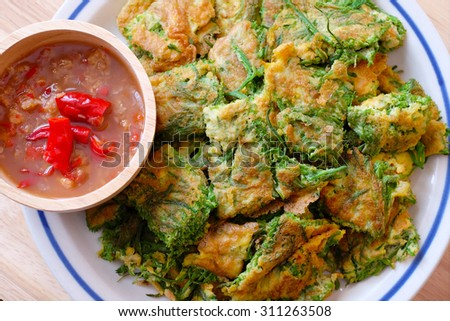 Fried acacia pennata omelet or cha-om egg with sauce of shrimp paste and chili (Nam prik kapi) on the wooden background, Thai Cuisine