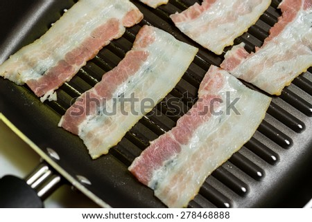 Fried bacon on skillet ; levels of cooked as you like it. - stock photo