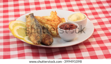 Fried baltic herring with fried potatoes, lemon and sauce on a checkered tablecloth - stock photo