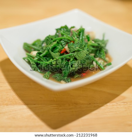 Fried bitter gourd leaf with oyster sauce , Thai style food - stock photo