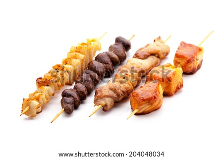 fried calamari, chicken hearts, chicken and salmon skewers on a white background - stock photo
