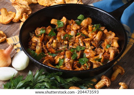 fried chanterelle mushrooms with onion and parsley in a frying pan and the ingredients on the table. horizontal