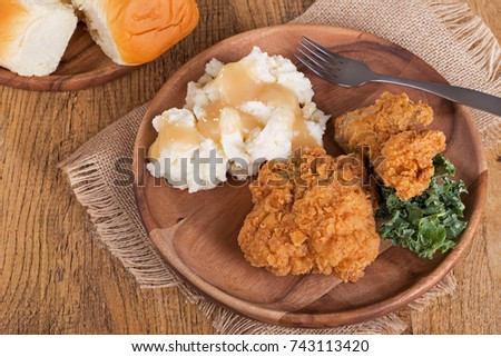 Fried chicken and mashed potatoes with dinner rolls on wooden plate