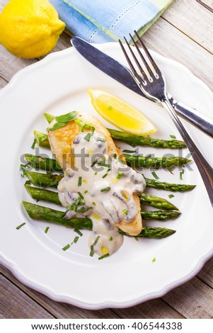Fried chicken breast on asparagus with tarragon and mushroom sauce. View from above, top studio shot