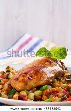 Fried chicken breast with sauteed vegetables: eggplant, carrot, zucchini, squash and tomatoes