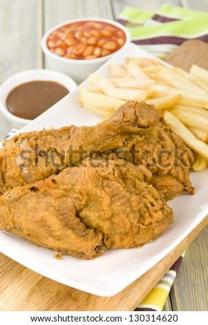 Fried Chicken & Chips - Chicken pieces on the bone coated in a spicy flour and deep fried served with fries, baked beans and gravy. - stock photo