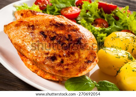 Fried chicken fillet, boiled potatoes and vegetable salad - stock photo