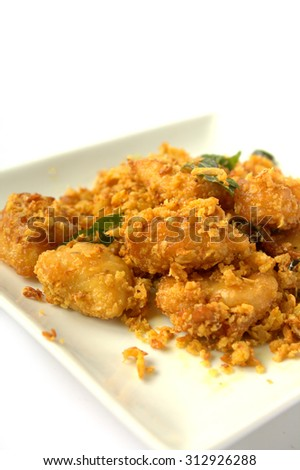 Fried Chicken fillet butter coated with egg floss and cereal. garnish with curry leaves. White background