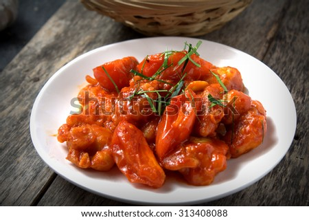 fried chicken fillet in tomato sauce