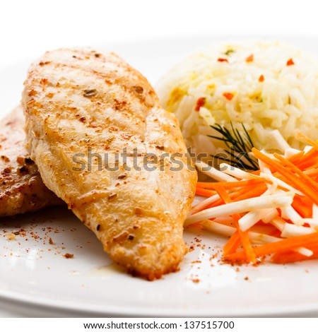Fried chicken fillet, white rice and vegetables - stock photo