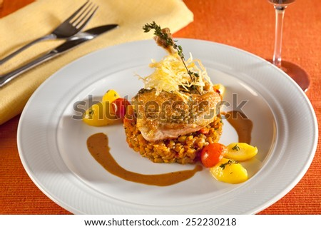 Fried chicken, guinea fowl, on red lentils with vegetables, red cherry tomatoes, potatoes and port wine sauce, decorated with very thin grilled crispy potato stripes.  - stock photo