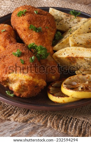 fried chicken legs dipped in batter, with a garnish on a plate close up on an old table vertical  - stock photo