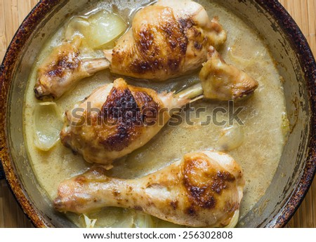 Fried chicken legs in a pan in a creamy sauce with onion - stock photo