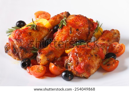 Fried chicken legs in tomato sauce with peppers, olives and rosemary on a white plate, horizontal closeup